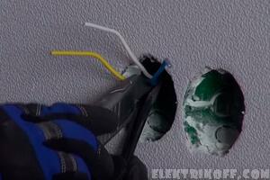 Электрик подключает розетку