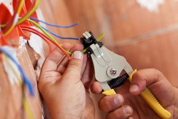 электрик обрезает провода, монтаж